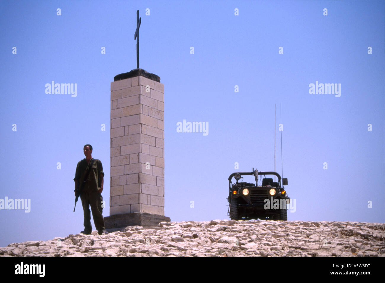 Soldier holding gun standing next to his jeep and stone column with crucifix on top under a blue sky,Israel. Stock Photo