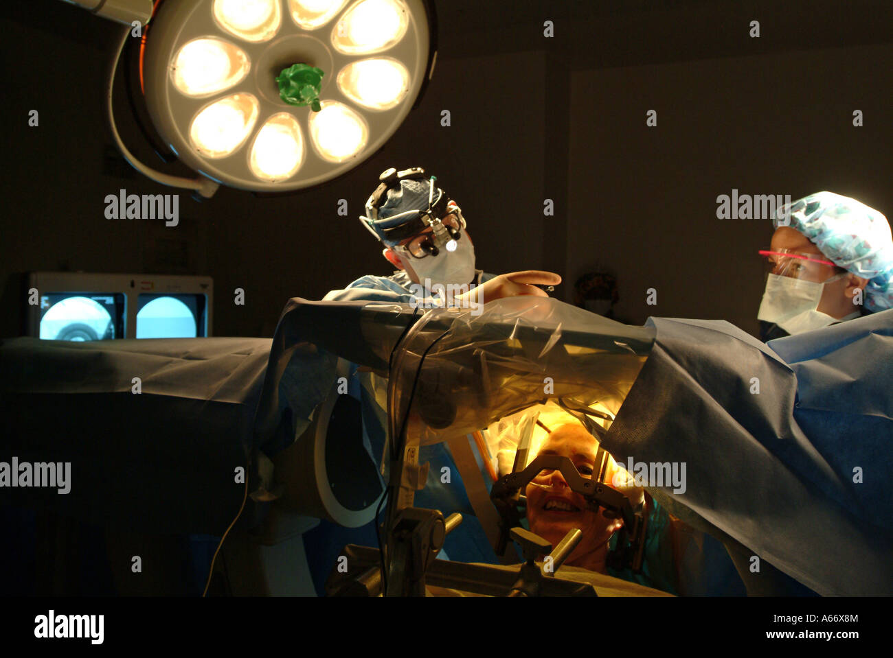 Brain surgeon performs a delicate brain procedure on an awake patient called Deep Brain Stimulation Stock Photo