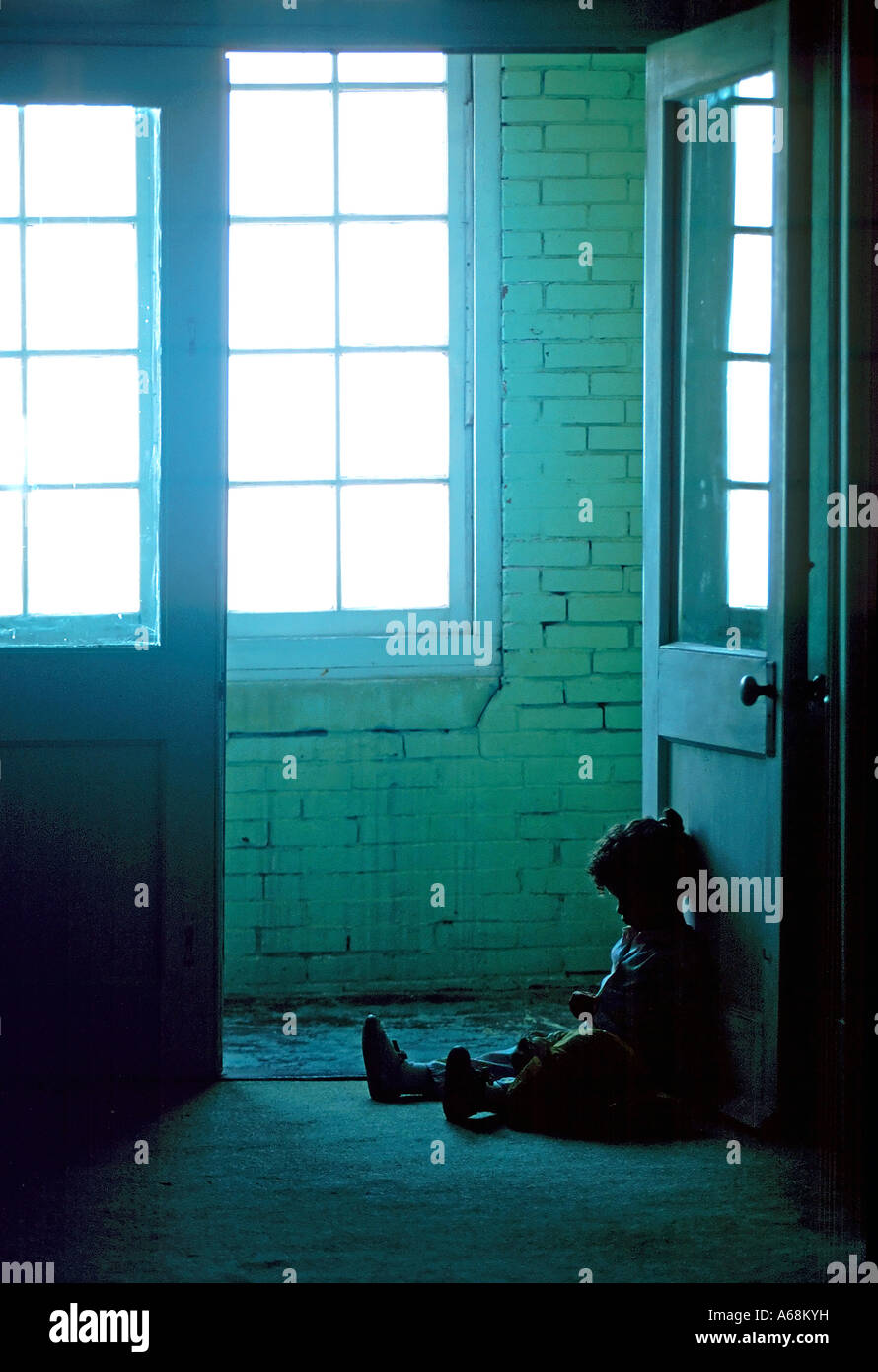 Small child sits alone in the dark dirty hallway of a rundown apartment building Stock Photo