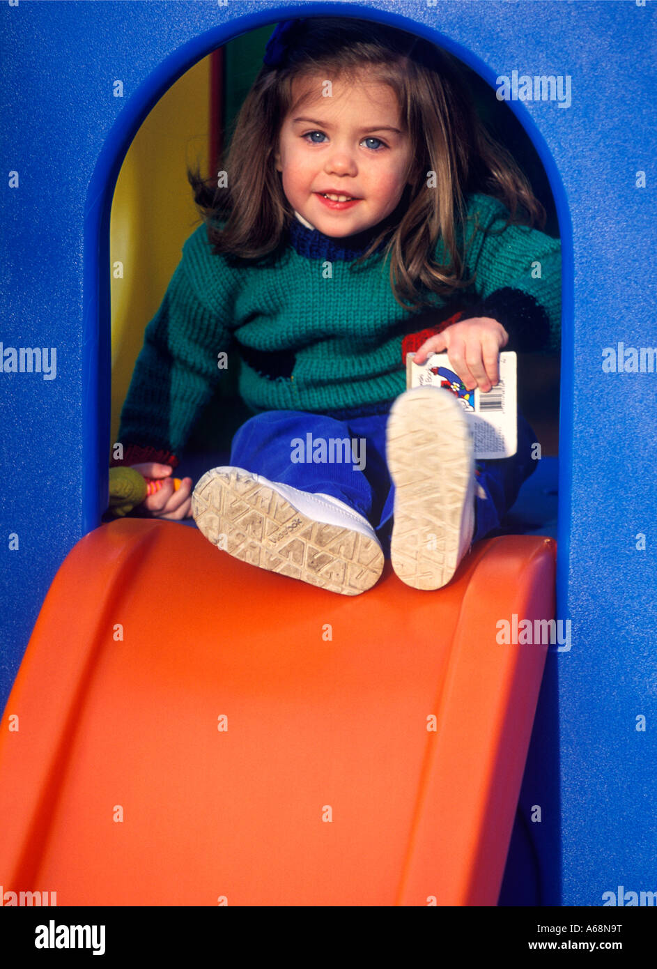 Toddler playing on playground sliding board - Stock Image