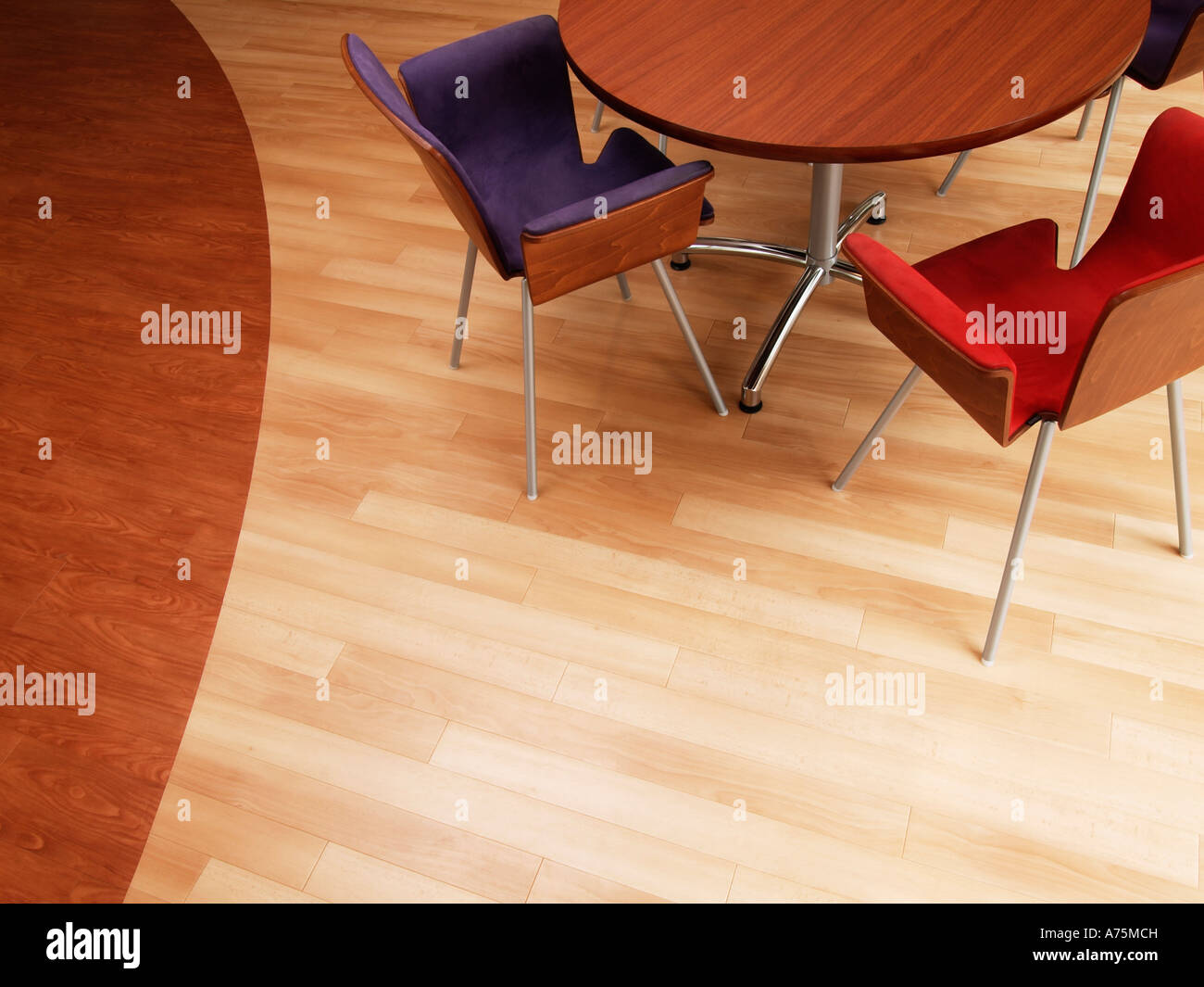 Birds eye view of round wooden table with modern design chairs on parquet floor made of two kinds of wood - Stock Image