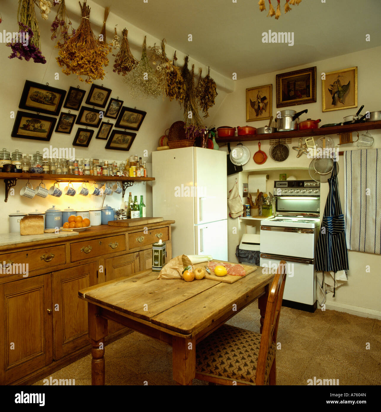 Dried flowers on sloping ceiling in small apartment kitchen with wooden dining table