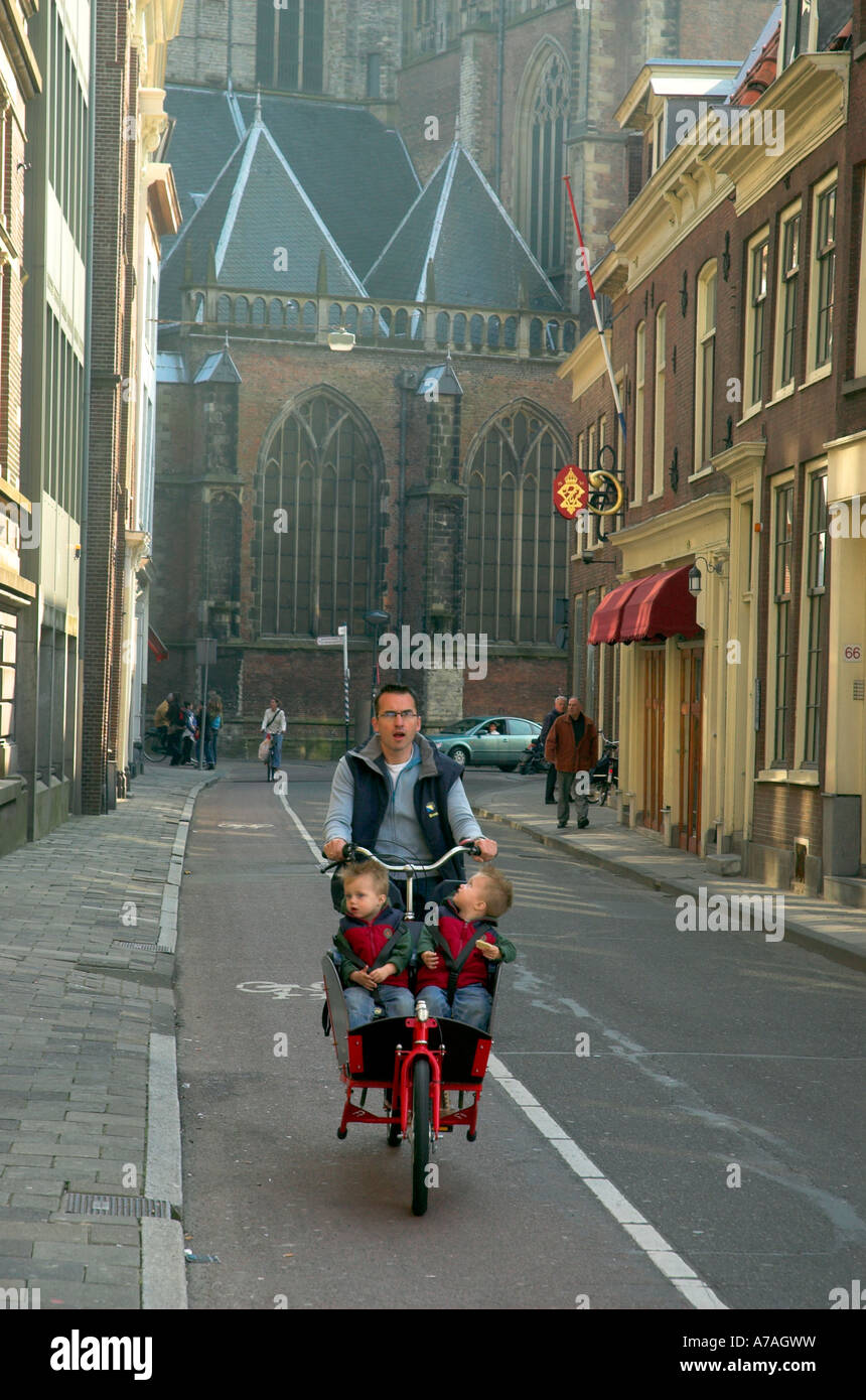 a-man-with-twins-on-a-bike-cycling-in-a-street-in-haarlem-withn-the-A7AGWW.jpg