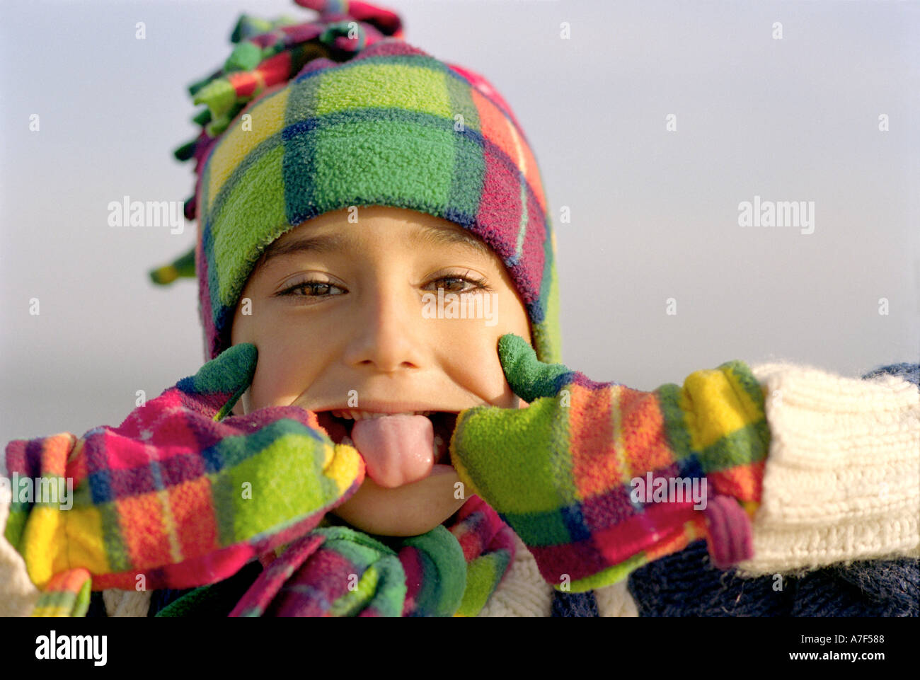 Portrait of cheeky young Indian boy pulling face at camera - Stock Image