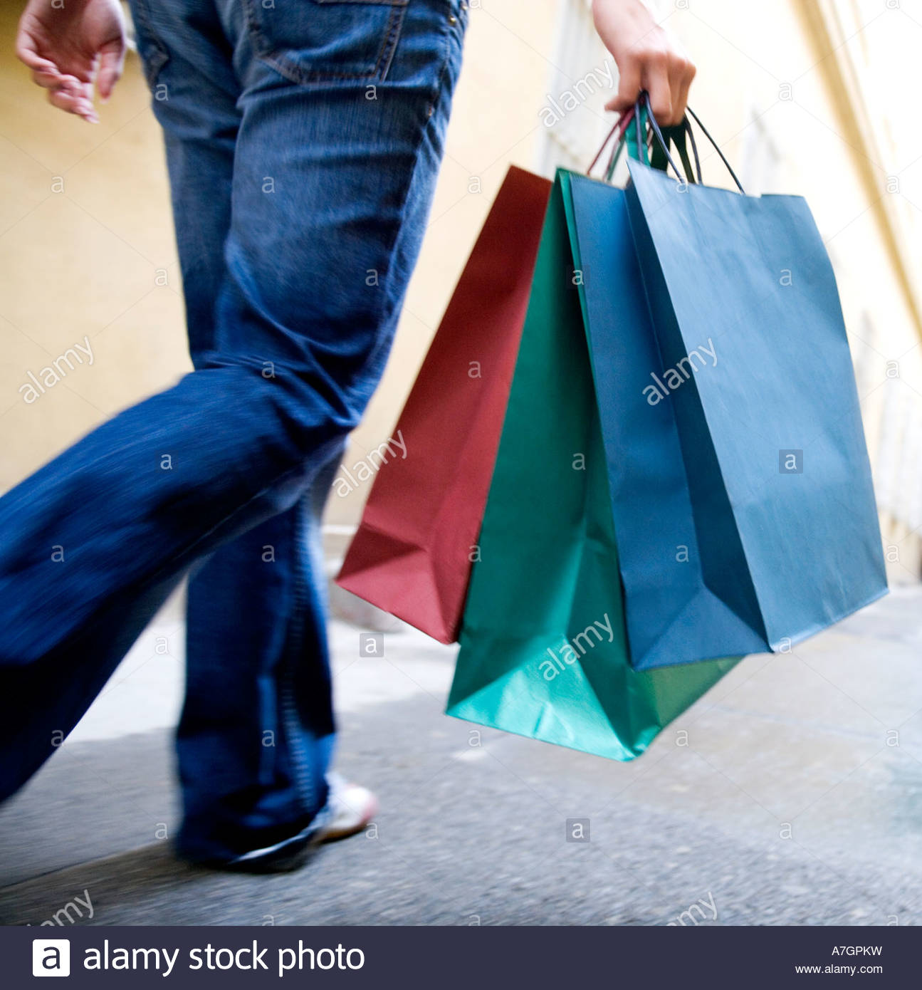A person carrying shopping bags - Stock Image