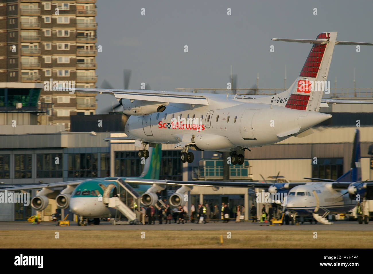 Scot Airways Dornier Do 328 110 landing at London City Airport and passengers boarding in the background 2004 - Stock Image
