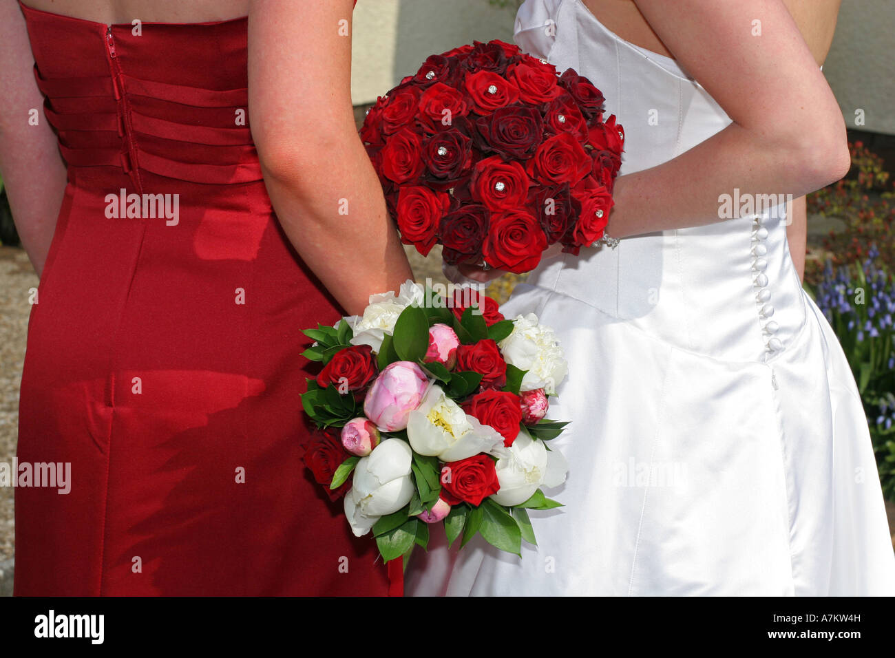 A bride in white wedding dress holds red rose flower bouquet on top a bride in white wedding dress holds red rose flower bouquet on top of red dress bridesmaids colourful flowers wedding day uk izmirmasajfo Choice Image