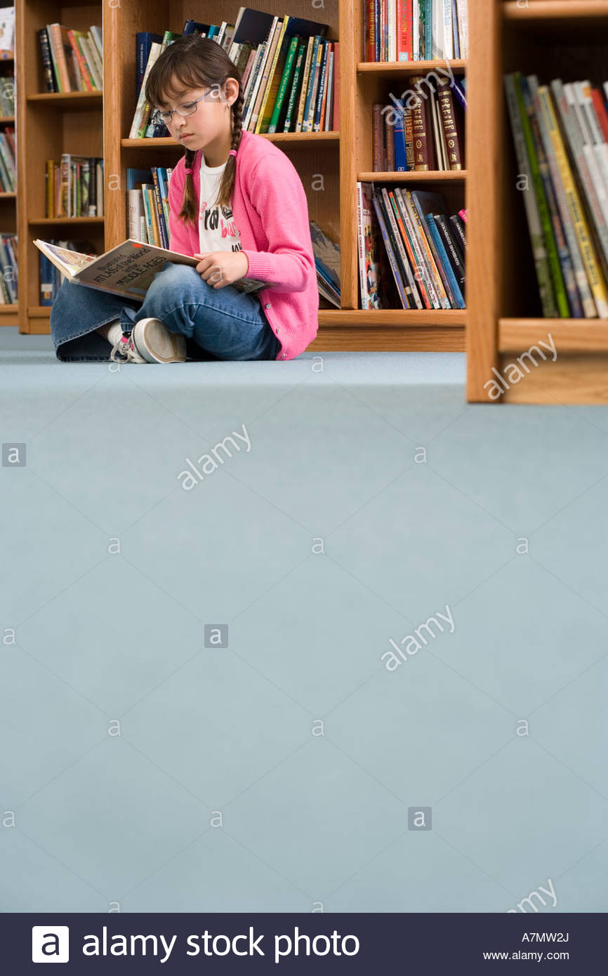 Girl 10 12 in spectacles sitting on floor beside bookshelf in library reading book surface level - Stock Image