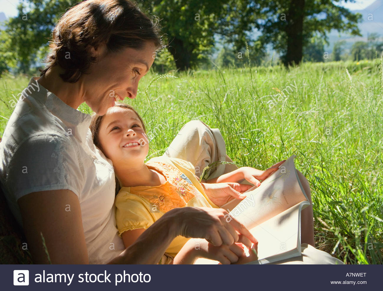 Mother reading storybook to daughter 8 10 in field smiling side view - Stock Image