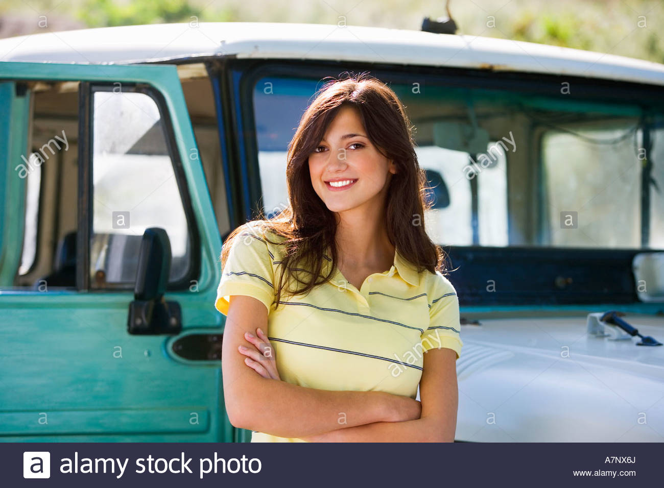 Young woman standing beside parked jeep arms folded smiling portrait - Stock Image
