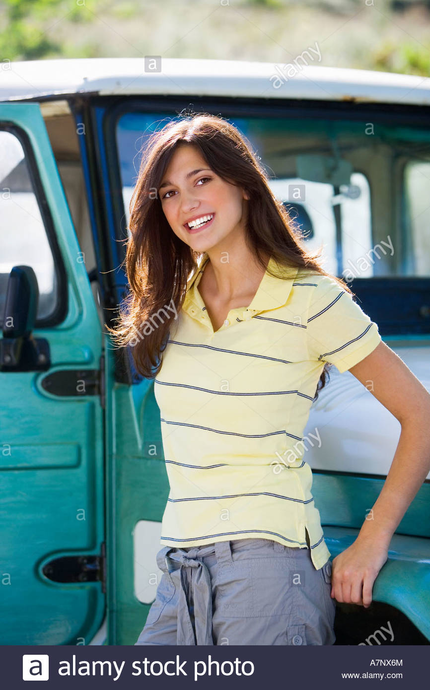 Young woman leaning against parked jeep smiling portrait - Stock Image