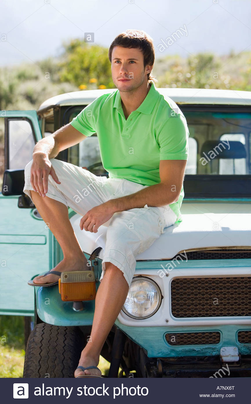 Young man in green polo shirt and white shorts sitting on bonnet of parked jeep - Stock Image