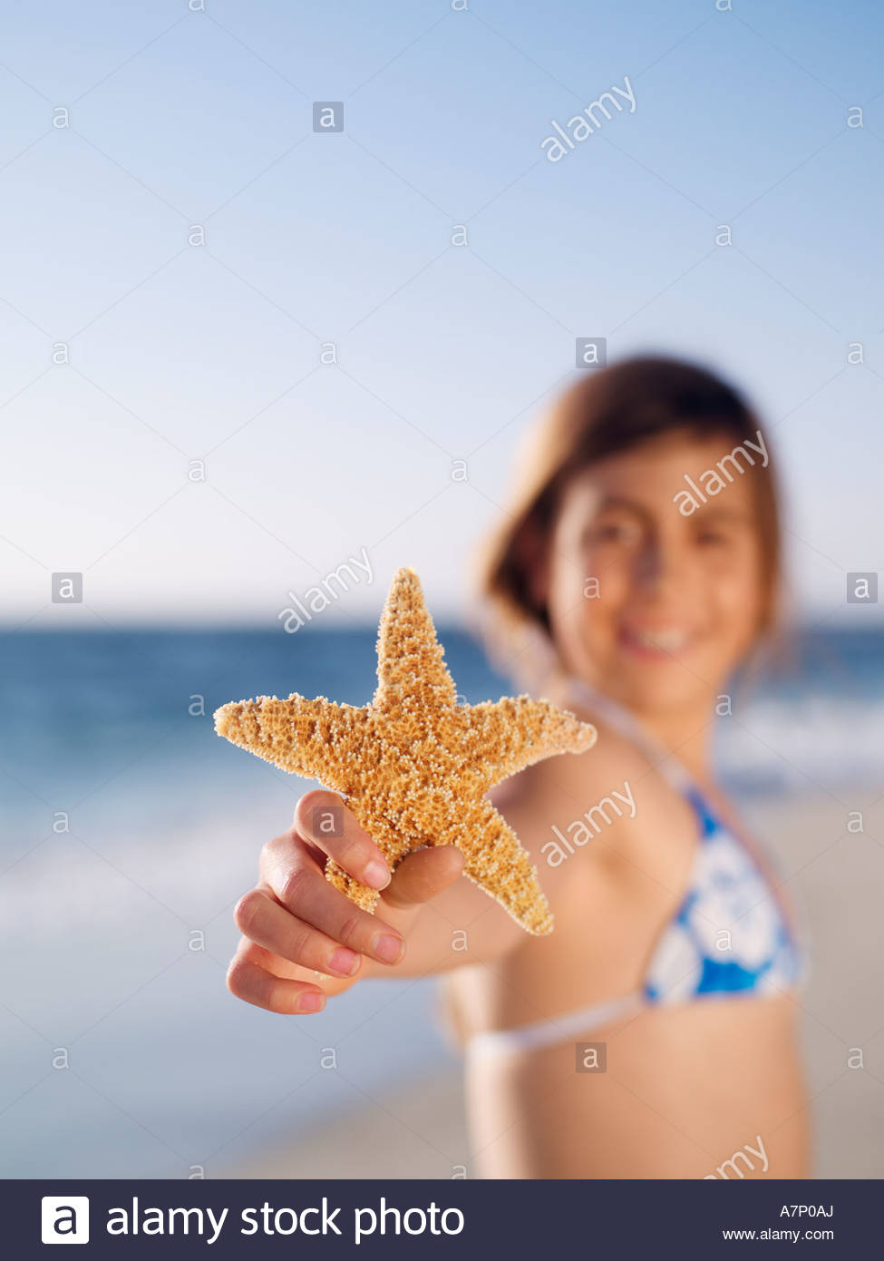 Girl 10 12 holding aloft starfish on sandy beach smiling portrait focus on foreground - Stock Image