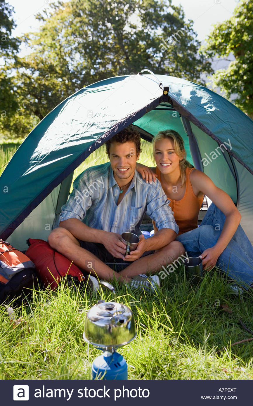 Young couple sitting inside dome tent in woodland clearing waiting for kettle to boil on camping stove smiling - Stock Image