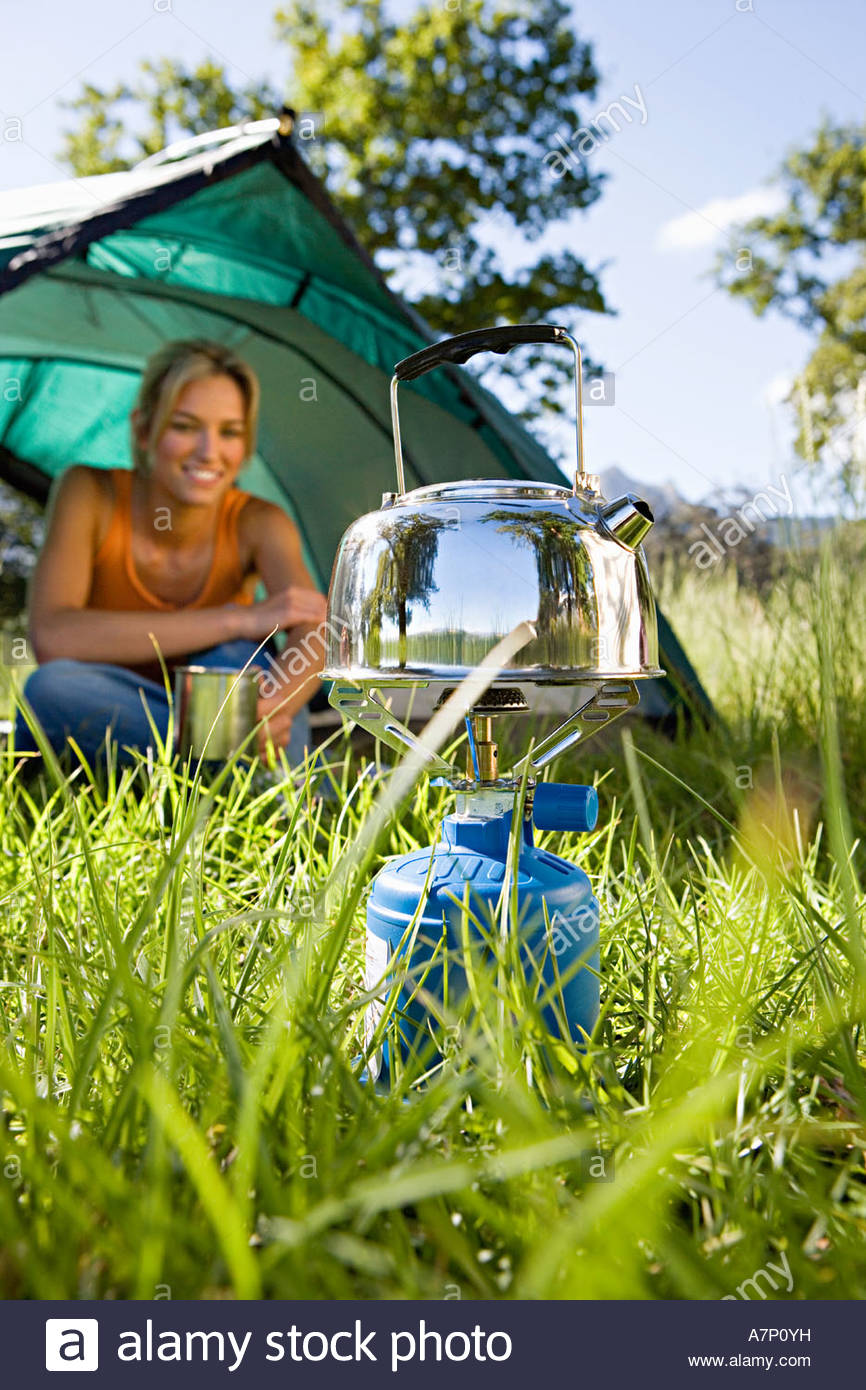 Young woman sitting inside dome tent in woodland clearing waiting for kettle to boil on camping stove smiling surface - Stock Image