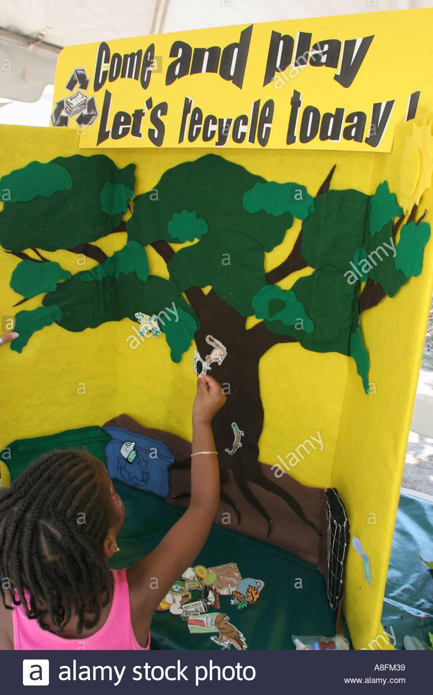 Miami Florida Little Haiti Earth Day Festival Black Haitian female student recycle exhibit game - Stock Image
