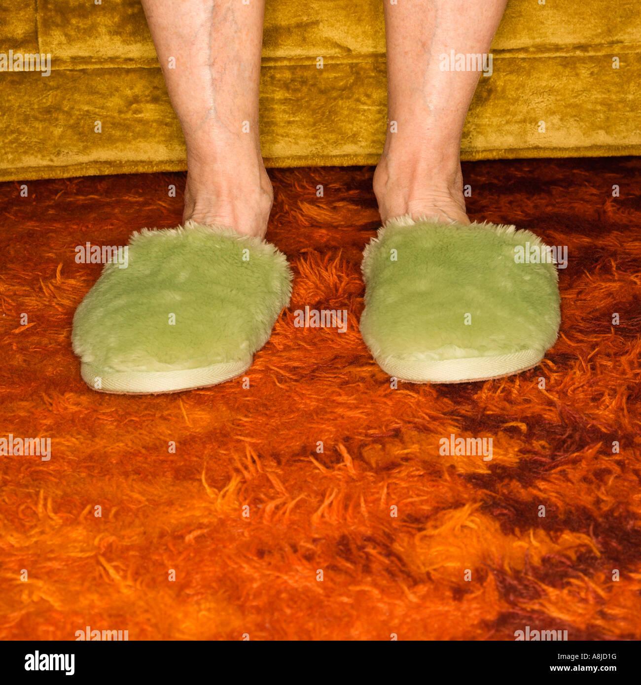 Caucasian senior female feet wearing green bedroom slippers on carpet Stock Photo