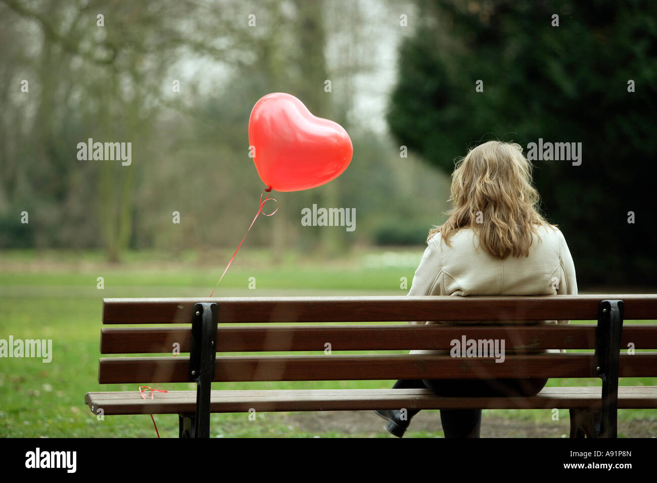 A young woman sits alone on a park bench - Stock Image