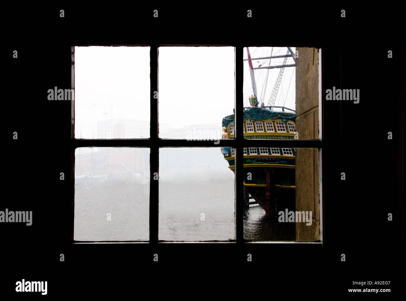 Historic sailing ship viewed from a multi paned window - Stock Image