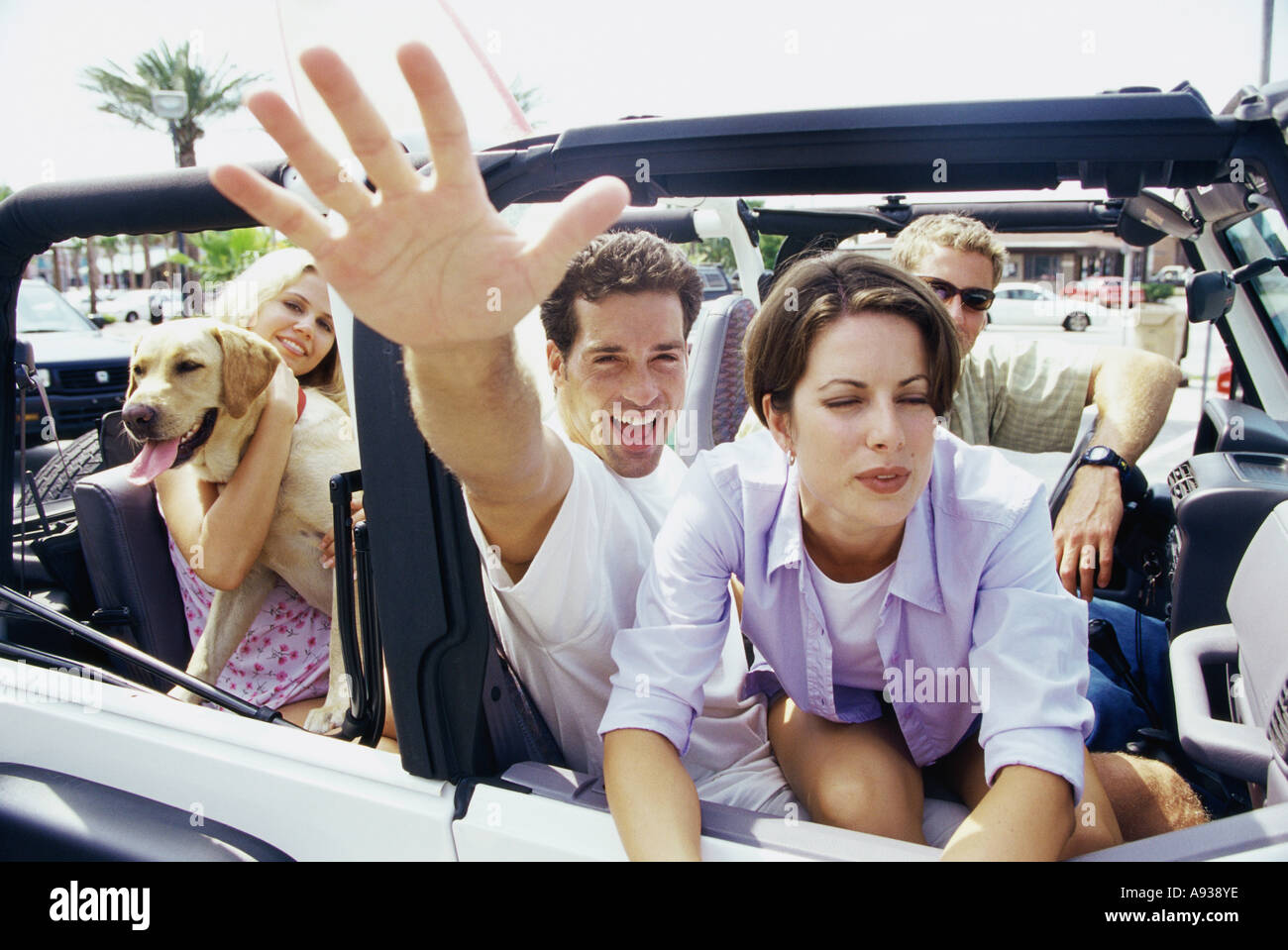 Close-up of two young couples sitting in a jeep - Stock Image