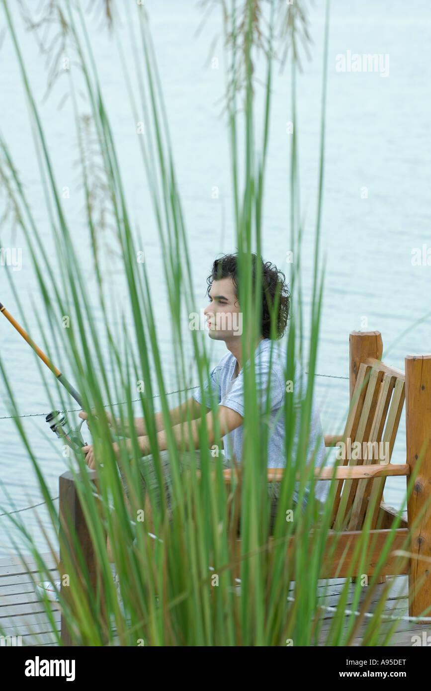 Young man sitting on dock, fishing - Stock Image