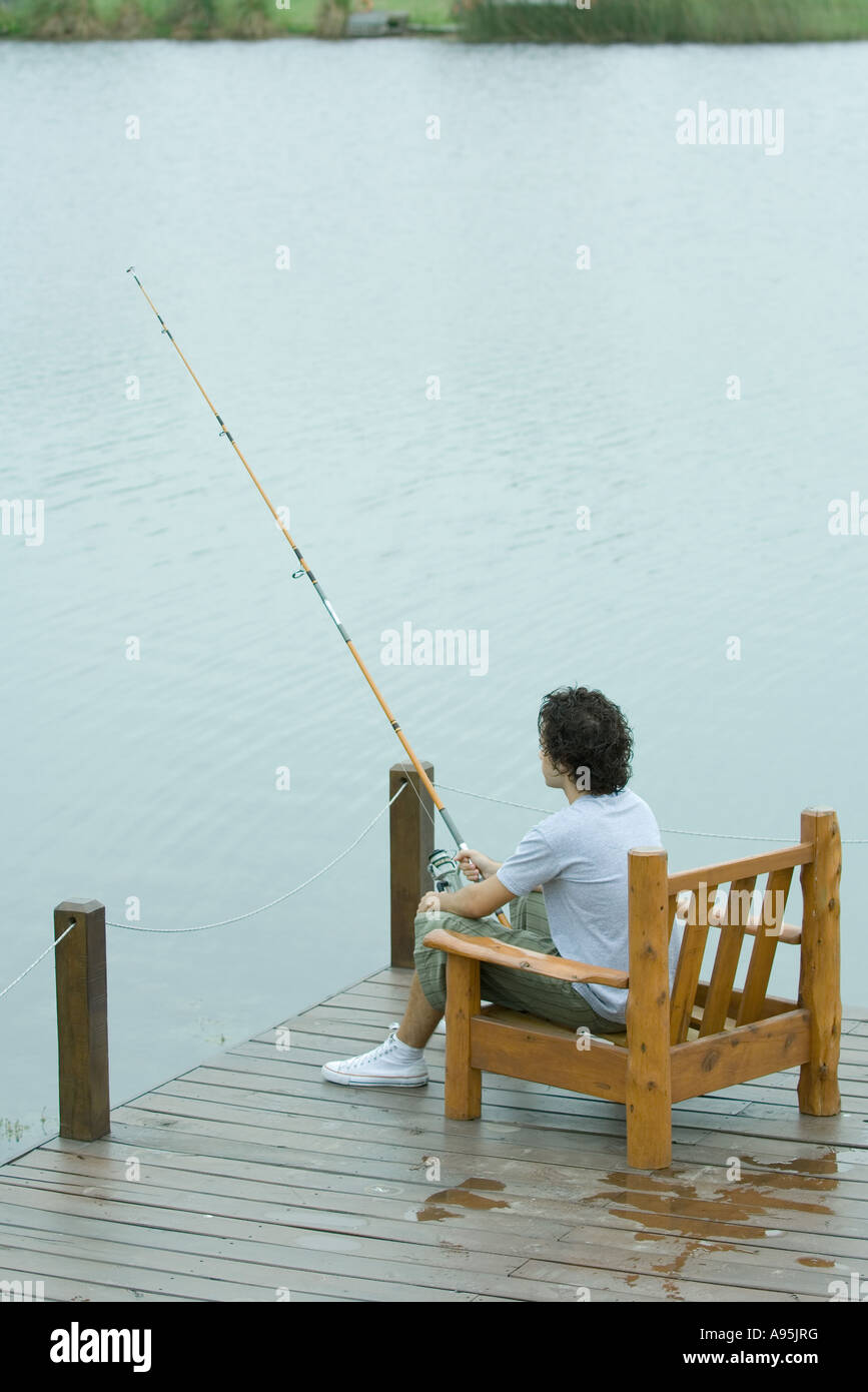 Young man fishing on dock - Stock Image