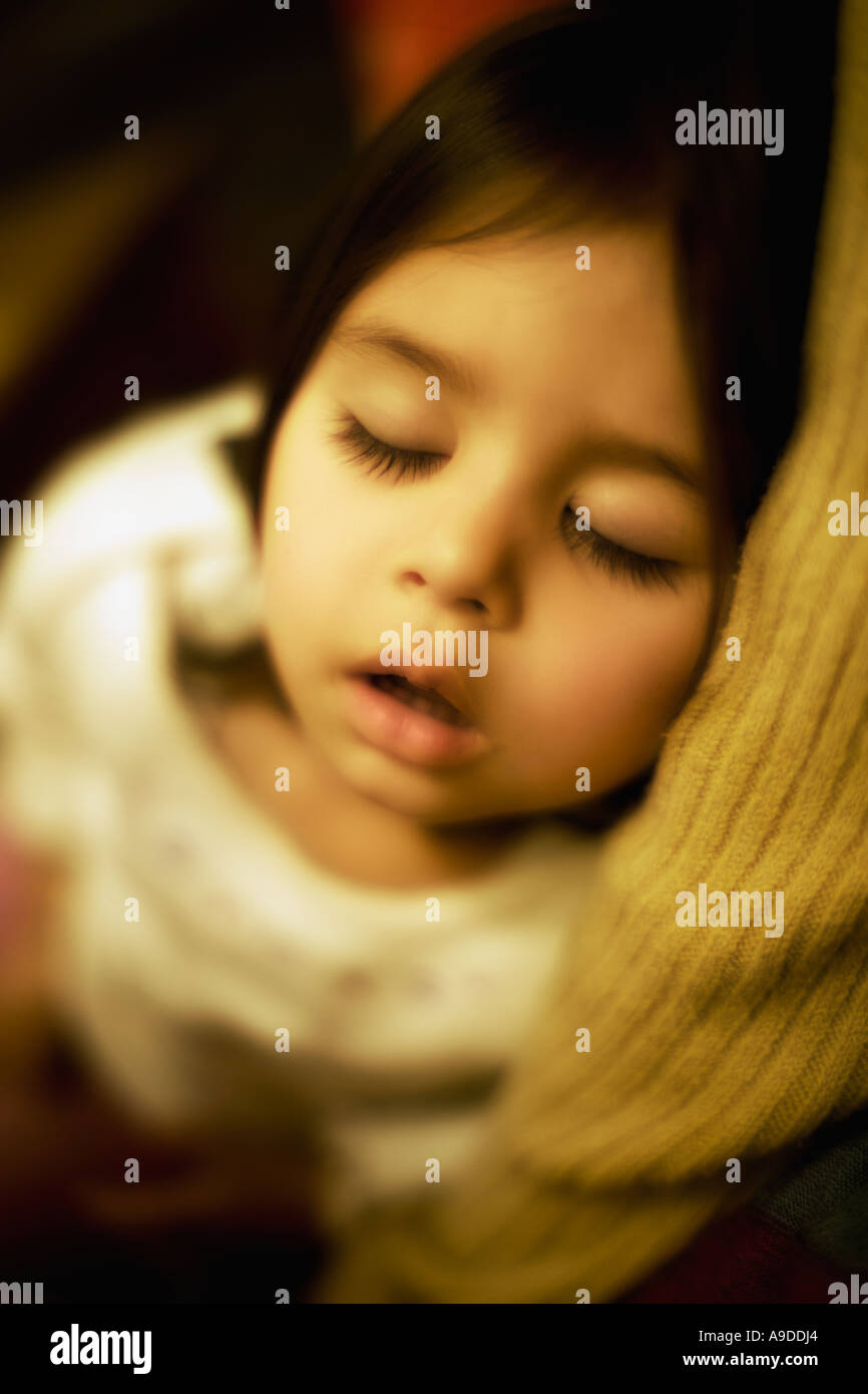 Head and shoulders portrait of two year old girl sleeping in the arms of her mother - Stock Image