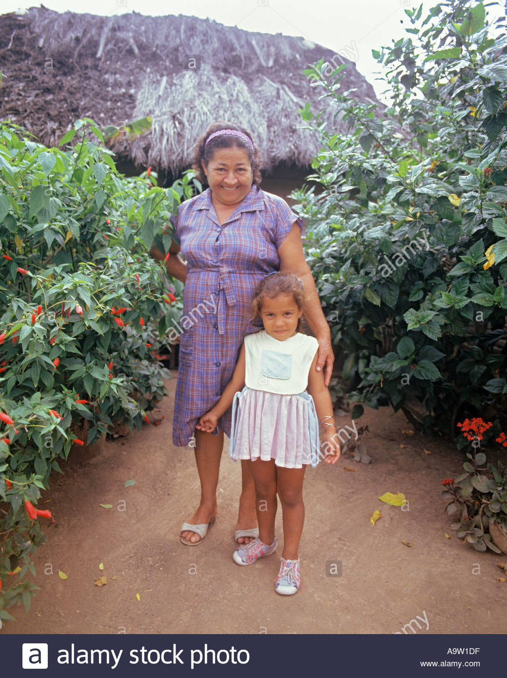 Grandmother and granddaughter in front of their farmhouse in the Sierra Maestra Mountains CubaStock Photo