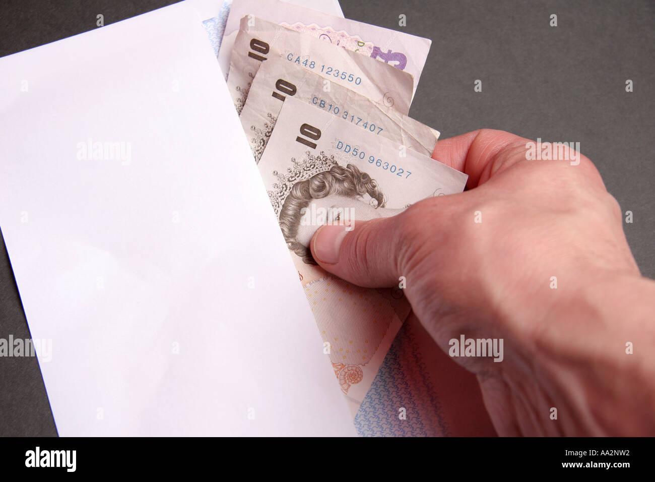putting cash in envelope - Stock Image
