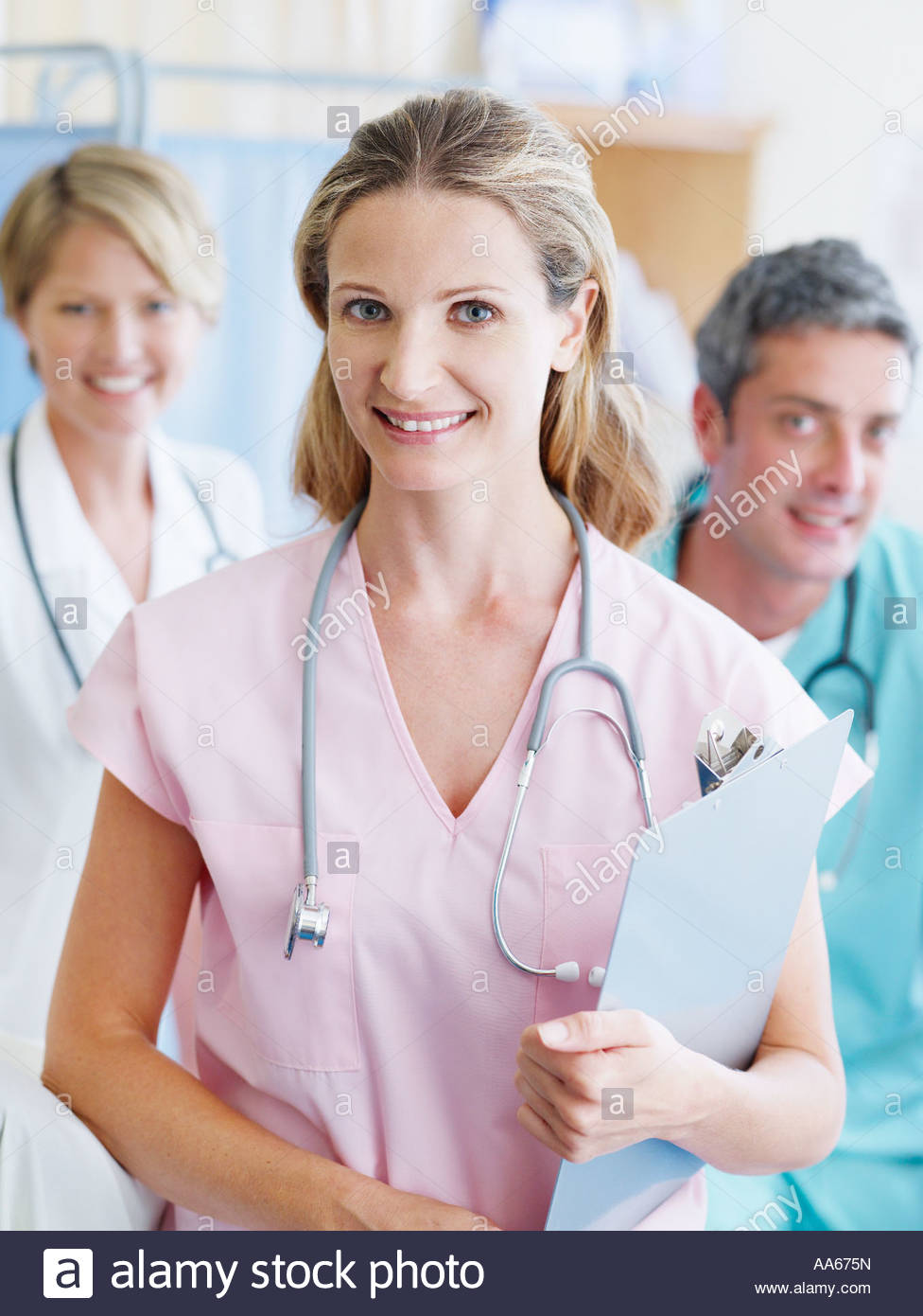 Three hospital workers smiling - Stock Image