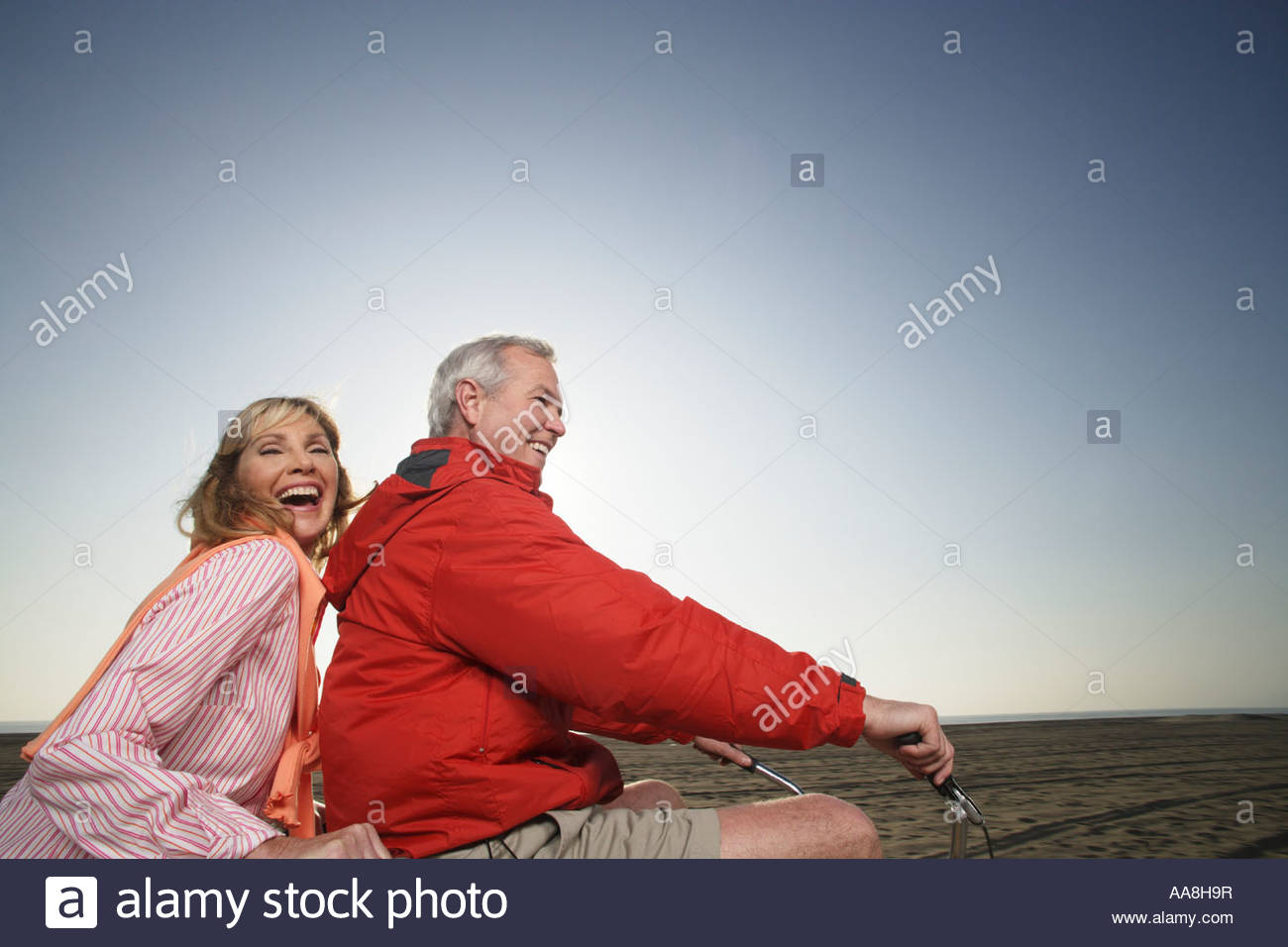 mature couple riding tandem bike on the beach stock photo: 12549826