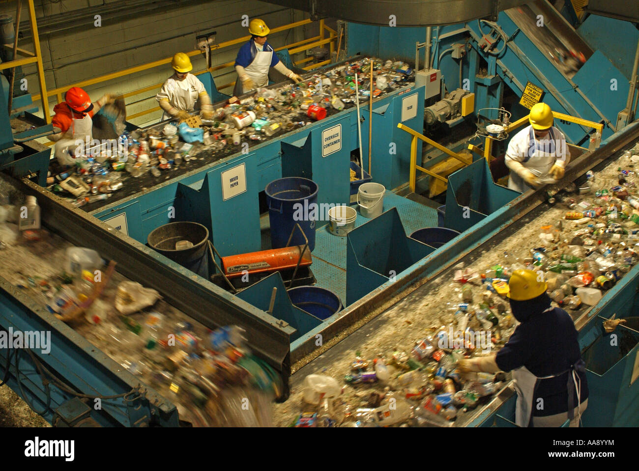 Workers are sorting through mixed material and separating the plastics metals and papers from the trash and glass Stock Photo