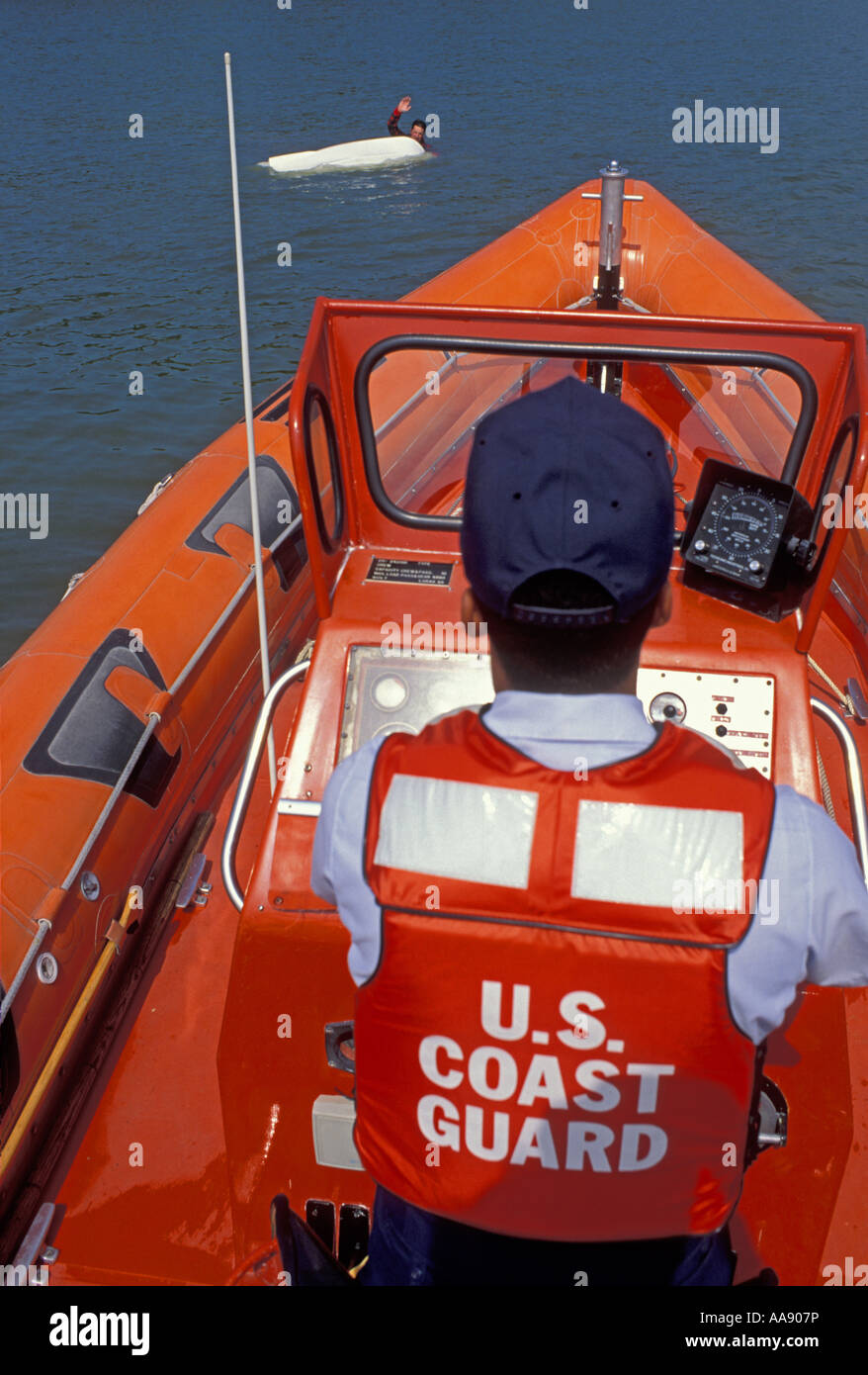 U S Coast Guard officer rescues a boater from an overturned water craft near Miami Florida Stock Photo