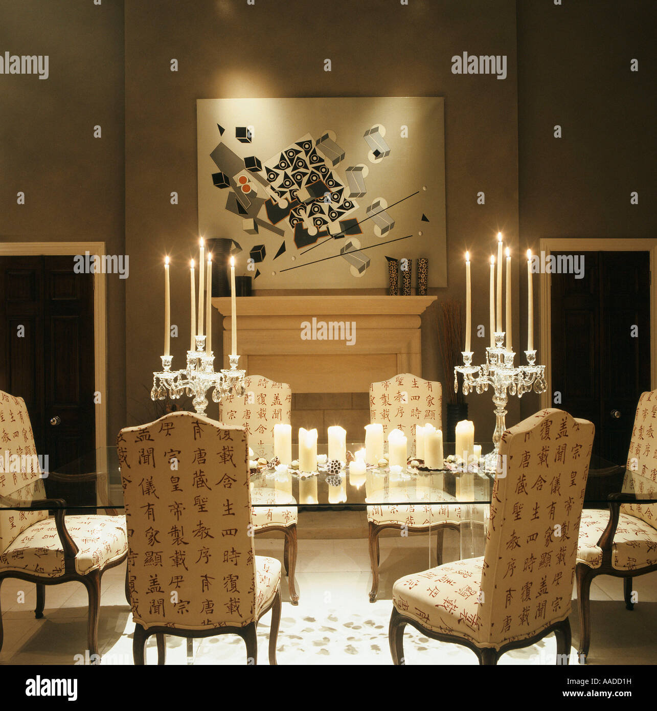 Glass dining table with upholstered chairs lit by candles and ...