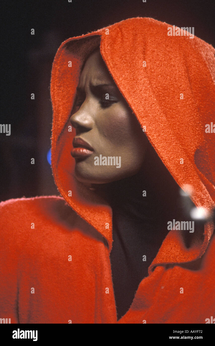 Grace Jones singer in profile facing left with red costume and hood PER0035 - Stock Image