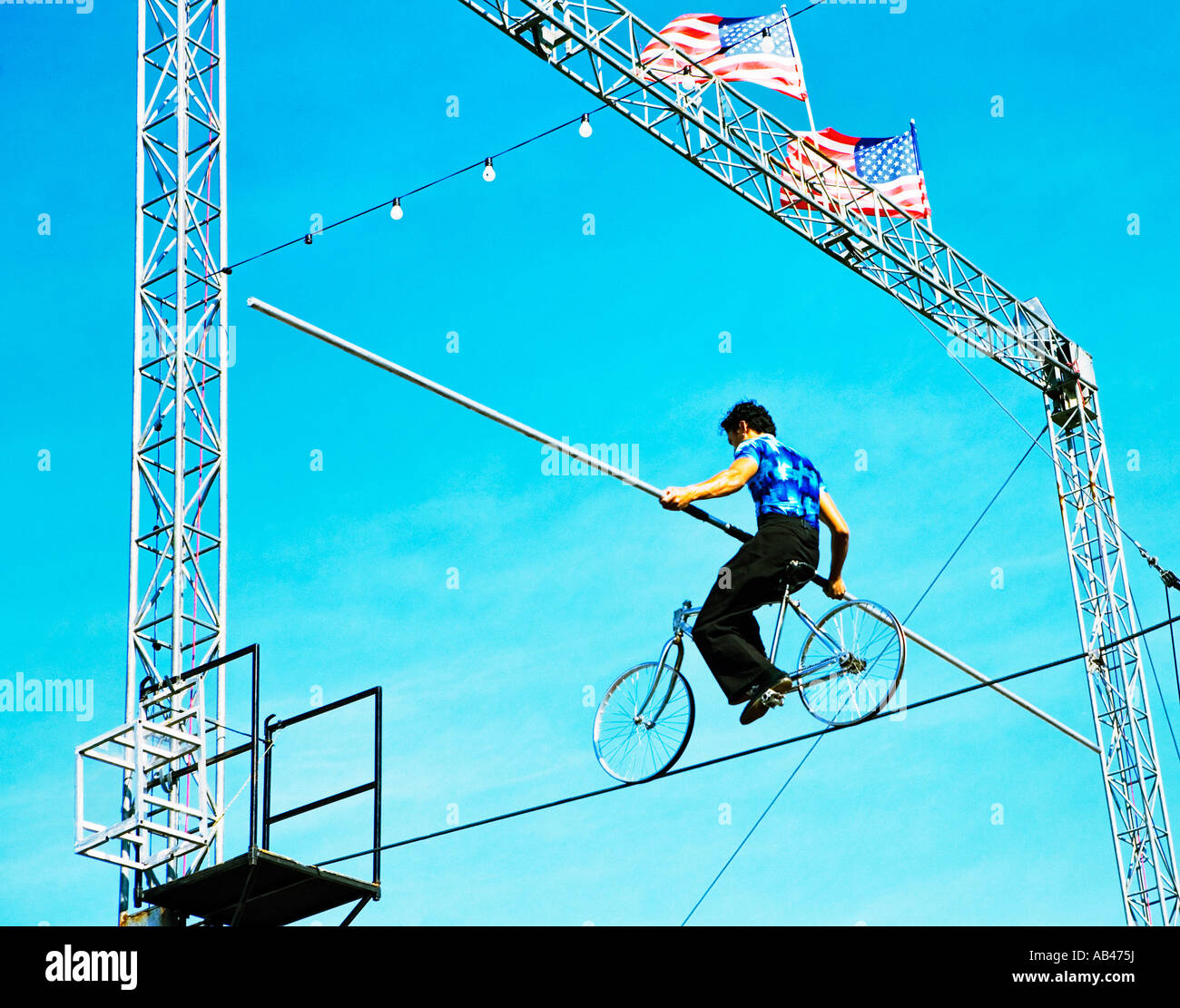 high wire walker riding bicycle set against blue sky with American ...