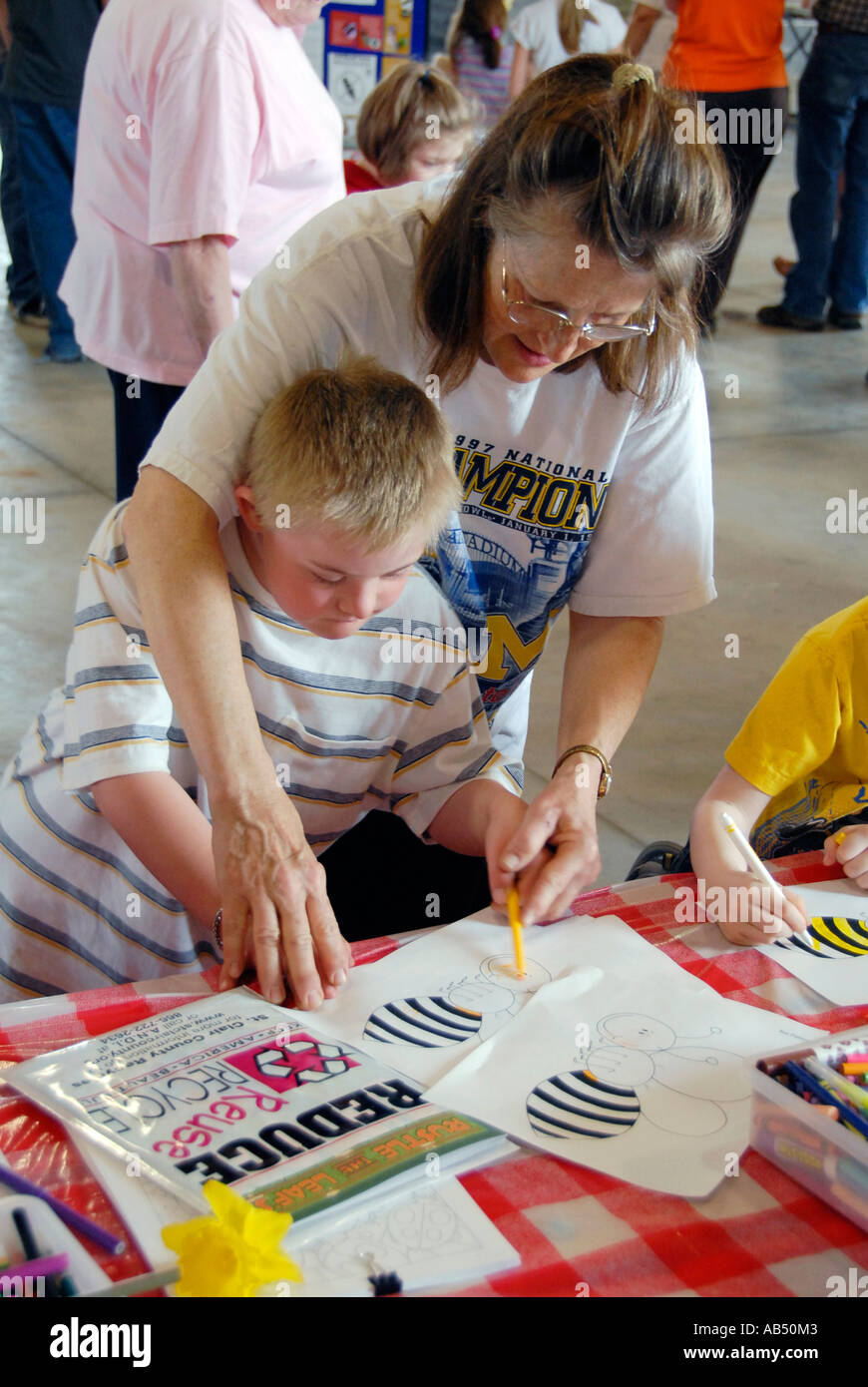 Mentally challenged youth colors a bumble bee at Earth Day Festival invites children and adults to learn about the - Stock Image