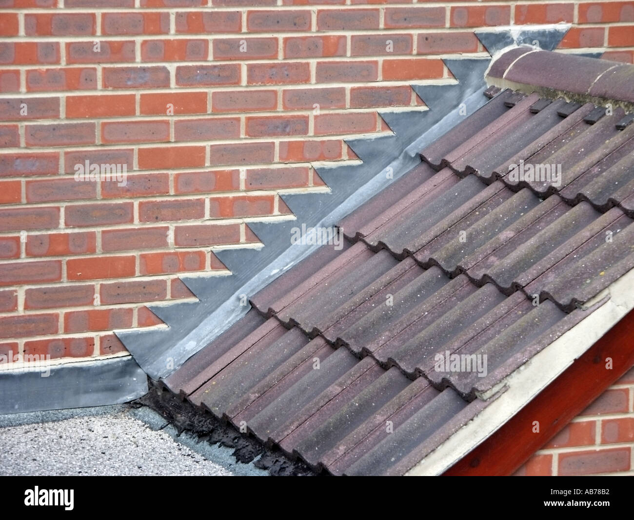 Close Up Of Building Construction Detailing Of Domestic Residential Roof  Abutment Of Garage Pitched And Flat Roof To Brick Wall