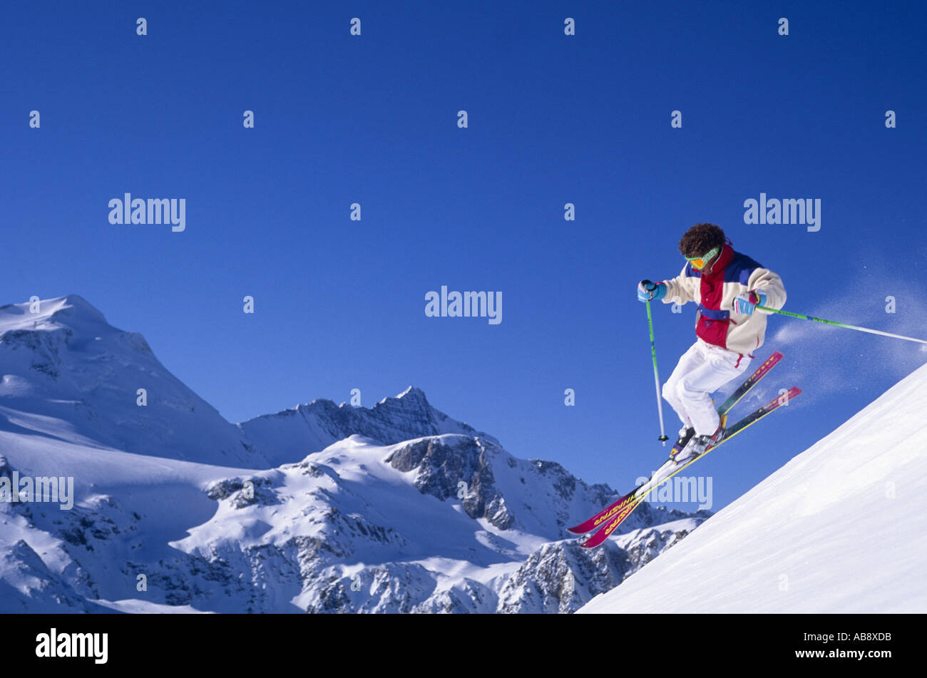skier racing down a piste, jumping, mountain tops in the background, France, Rhne-Alpes, Tignes. - Stock Image