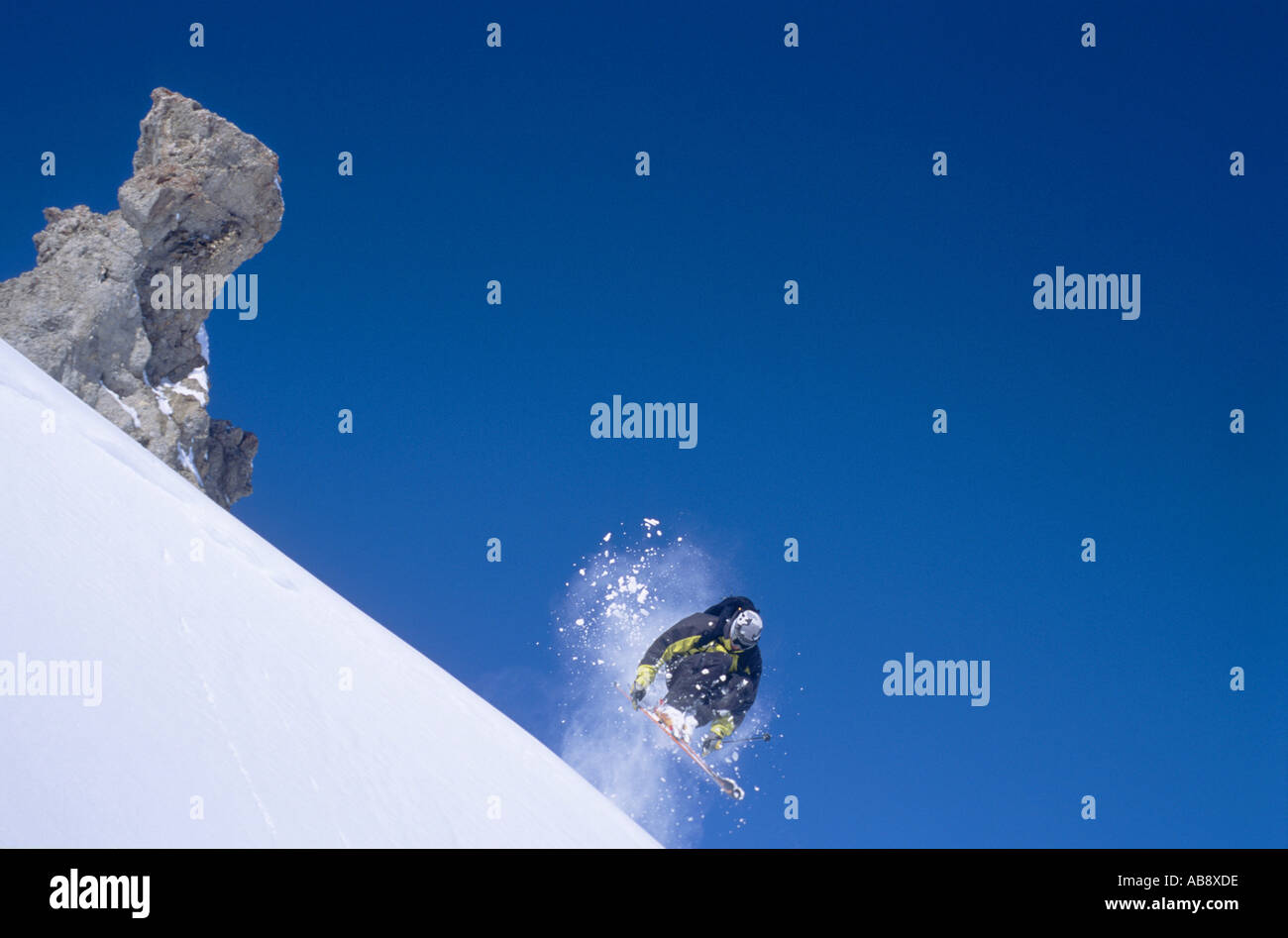 skier racing down a steep slope, jumping, leaving bizarrely shaped rock behind, France, Rhne-Alpes, Tignes. - Stock Image