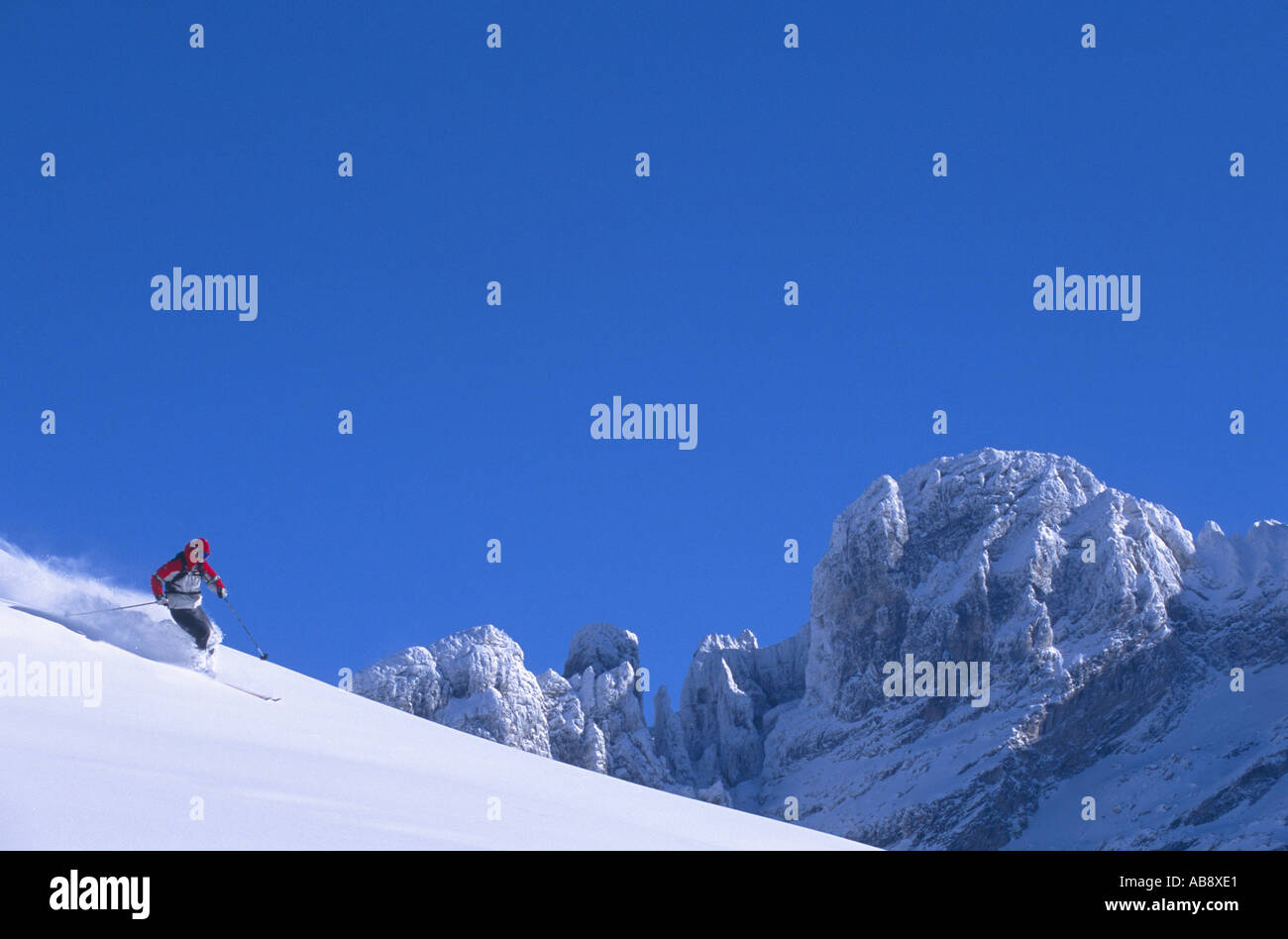 skier racing down a piste, mountain tops in the background, France, Rhne-Alpes, Courchevel. - Stock Image