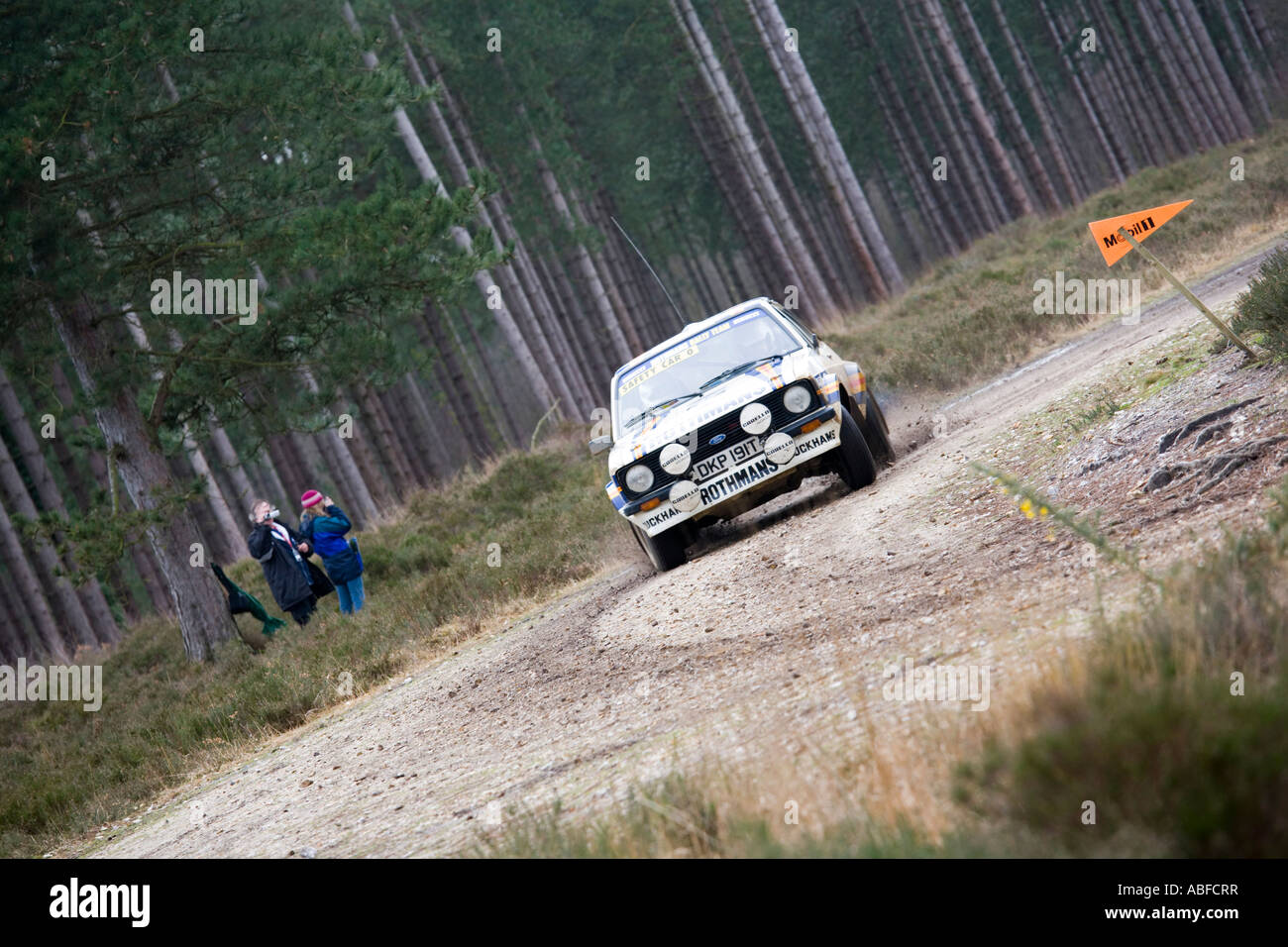 White Ford Escort rally car driving action spraying gravel stones ...