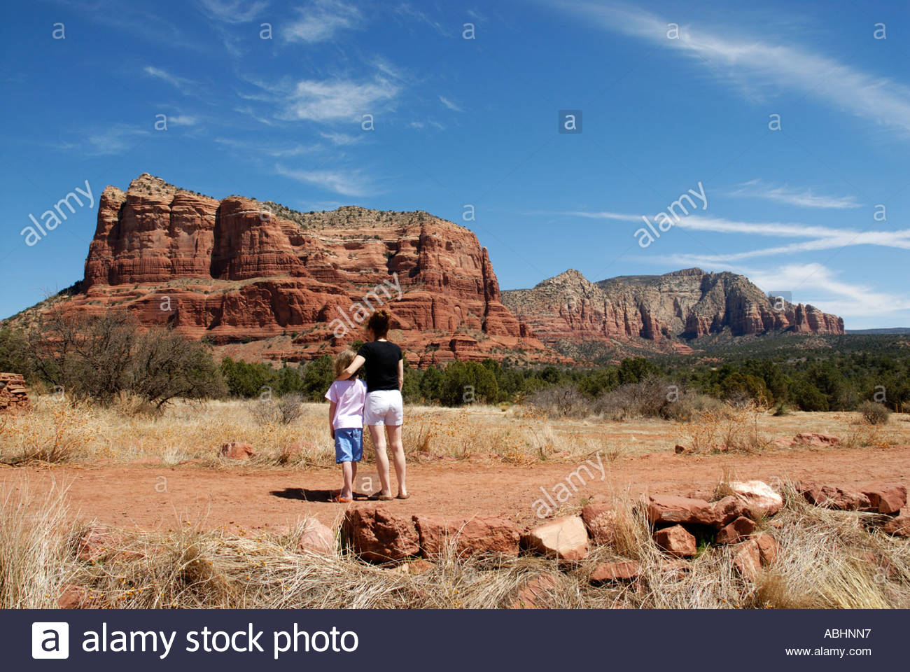 mother and daughter on trail path in Red Rock Country, near Sedona, Arizona looking at Couthouse Butte - Stock Image