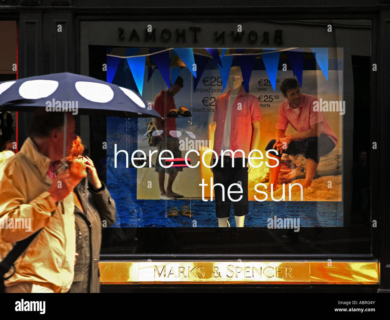 Man with umbrella in front of summer advertising - Stock Image