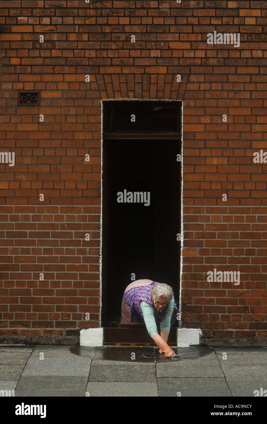 Woman Washing Front Door Step Pavement Outside Terraced Red Brick House  North Of England. Circa 1975 HOMER SYKES