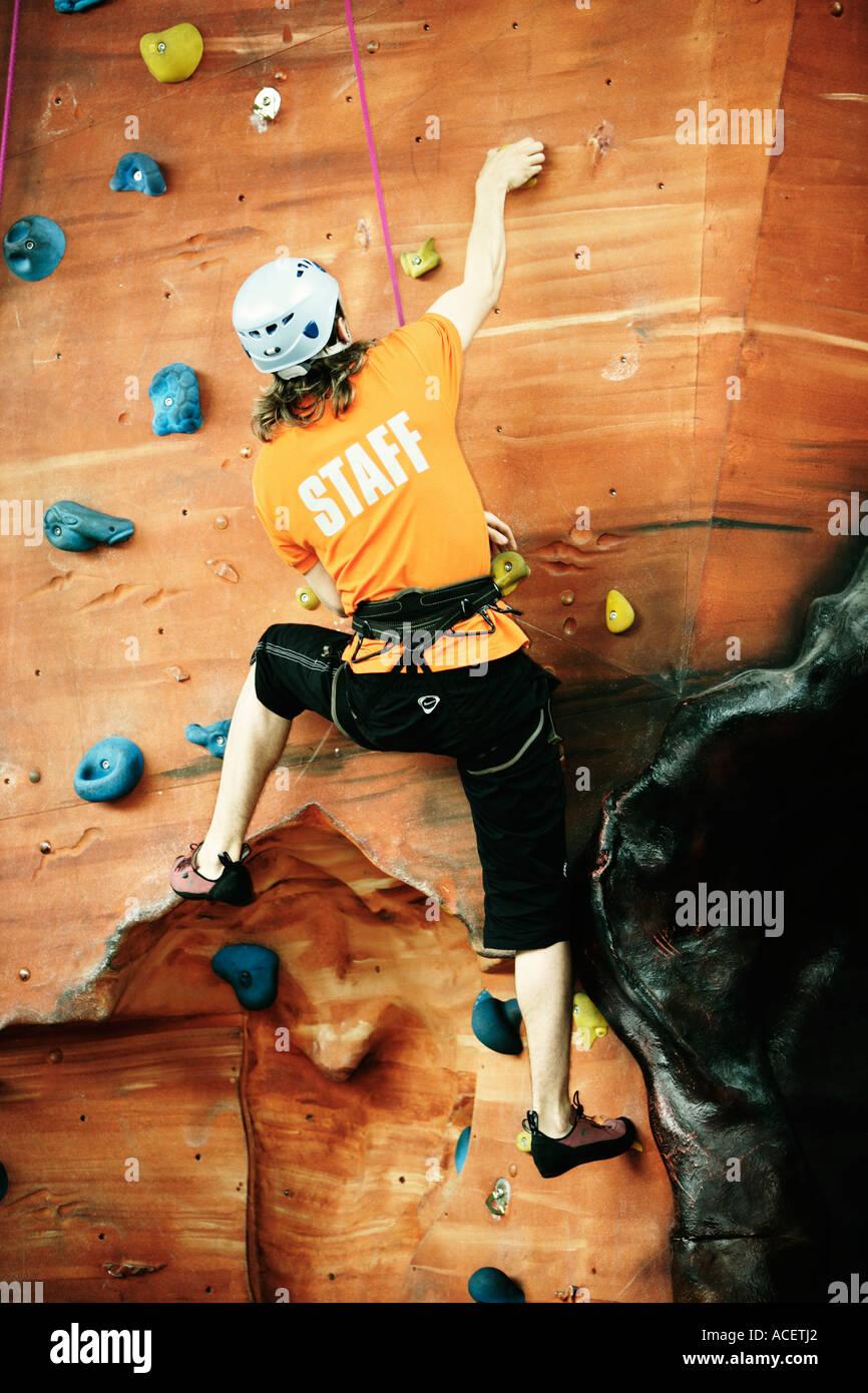 Male climber on indoor rock climbing wall UK - Stock Image