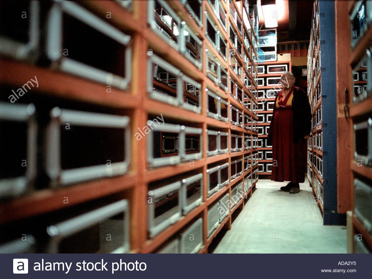 Head of the Bhutan national library looking down the archive of prayer carvings - Stock Image