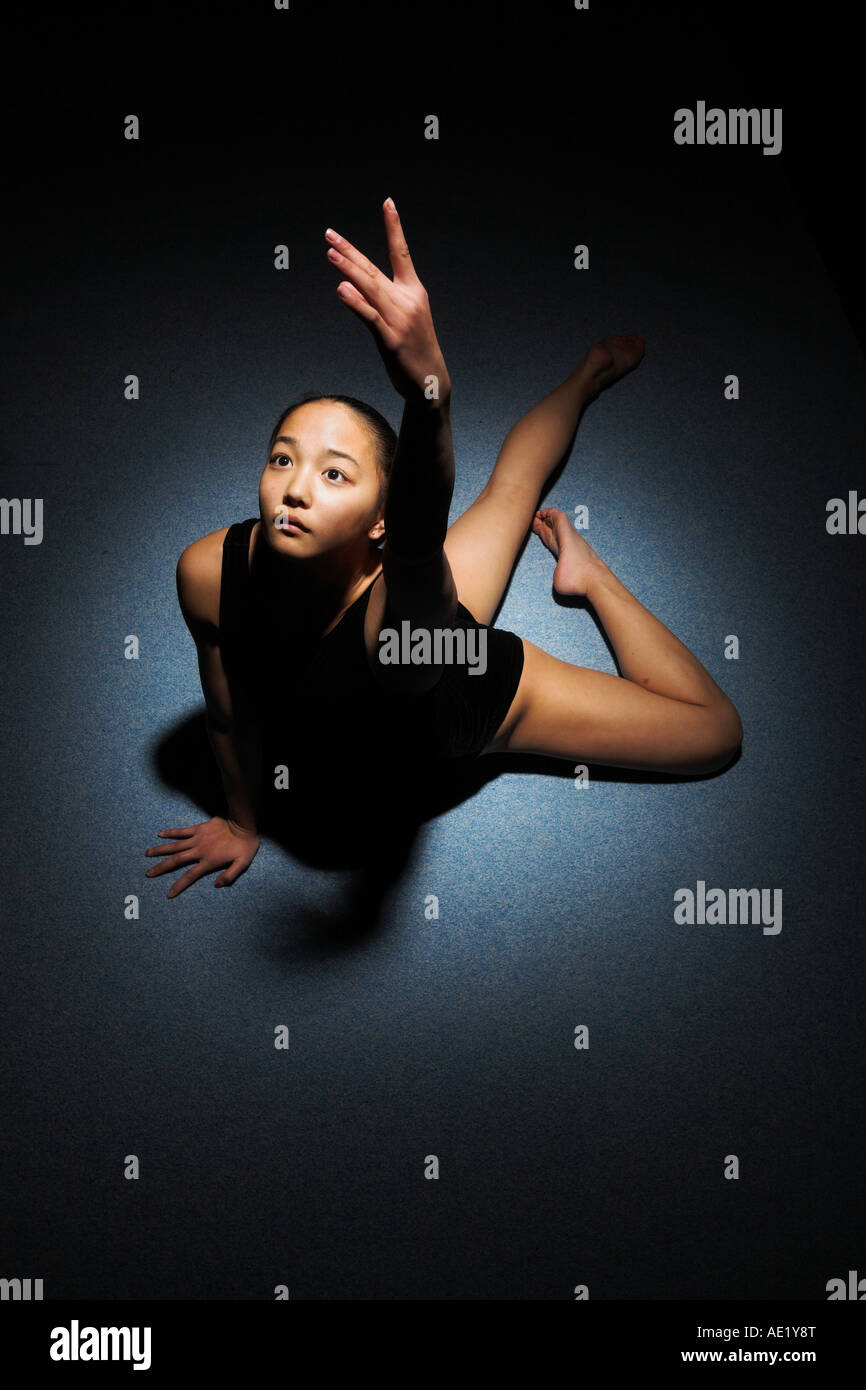 A gymnast on the floor reaching towards the light - Stock Image