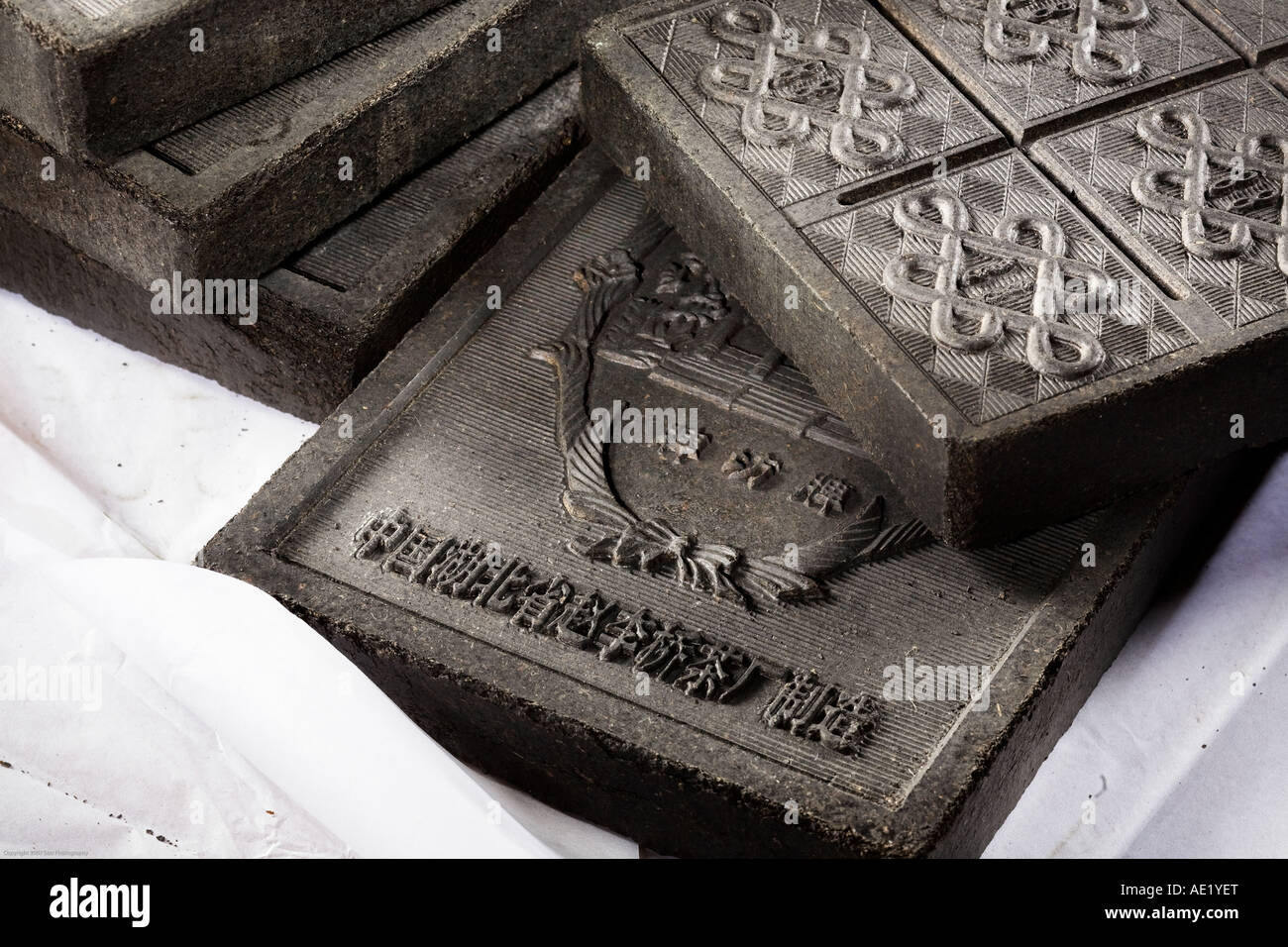 Richly embossed tea bricks stacked atop one another. Stock Photo