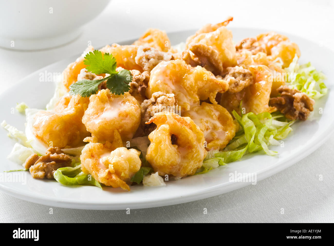 Honey walnut crispy shrimp prawn mayonaise oyster sauce chinese food with green onion dish white plate delicious - Stock Image
